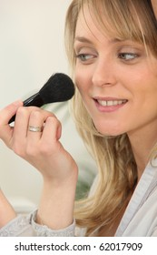 Portrait of a woman making up with a brush
