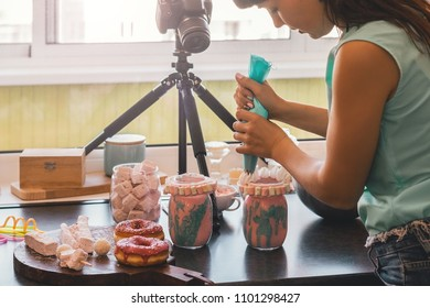 Portrait of woman making a video blog using SLR camera about cooking a turquoise-pink milkshake in glass jars on her domestic kitchen. Copy space.