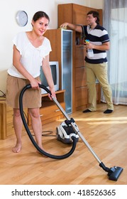 Portrait of woman and man cleaning flat after work