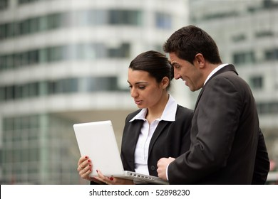 Portrait of a woman and a man in front of a laptop computer