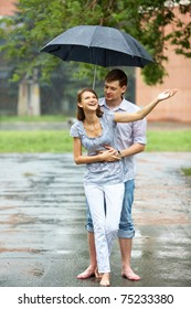 Portrait of woman and man walking under umbrella during rain