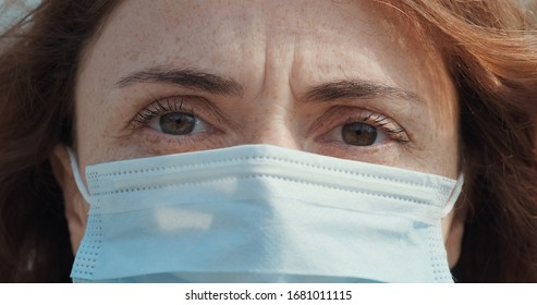 Portrait woman medical mask her face red hair fluttering in wind during quarantine virus Coronavirus COVID-19, stands in park looks anxiously into distance. Epidemic, pneumonia, pandemic. Close-up