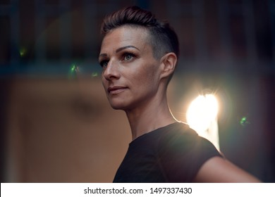 Portrait of woman with mohawk hairstyle standing in front of the building entrance