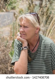 Portrait of a woman in the nature, with grasses in the background. Natural, soft charisma, positive, slightly thoughtful expression, blonde hair, sunglasses pushed on the head, green, white top.