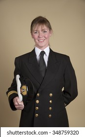 Portrait of a woman naval Lt Commander in uniform and holding her hat under her arm