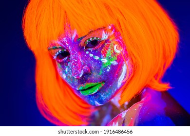 Portrait of woman in with neon makeup. Fluorescent paint in ultraviolet light