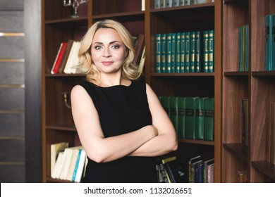 Portrait of a woman in the office on the background of bookshelves. The concept of a specialist in his field