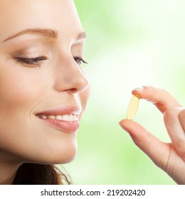 Portrait of woman with Omega 3 fish oil capsule, outdoor