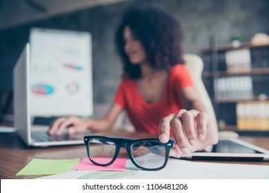 Portrait of woman on blurred background sitting at desktop browsing on laptop holding  focused protective optical eye glasses for computer bad vision. Test examination health care concept