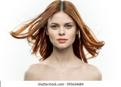 Portrait of a woman on a light background hair in the wind