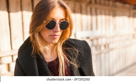 Portrait of a woman on the street.Girl in sunglasses cover the eyes from the bright sun