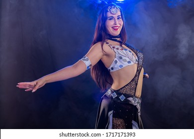 Portrait of a woman in oriental costume performing belly dance. Tribal fusion dance concept.