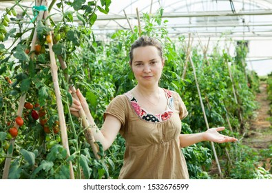 Portrait of woman owner of hothouse business standing near growing vegetables
