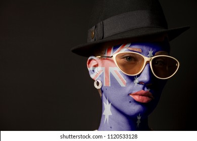 Portrait of woman with painted australia flag and sunglasses on black background