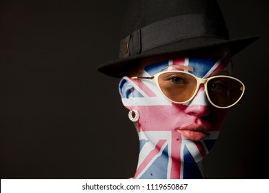 Portrait of woman with painted british flag and sunglasses on black background
