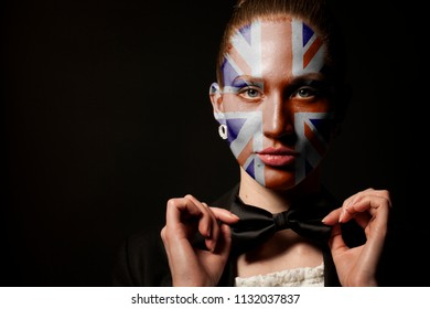 Portrait of woman with painted British Union Jack flag and bow tie on black