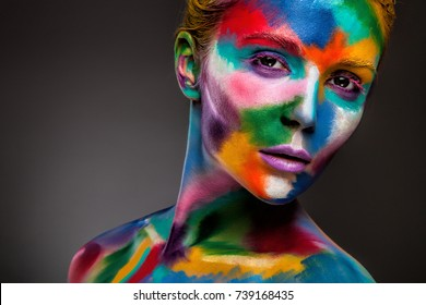 Portrait of a woman with a painted face. Creative makeup and bright style.