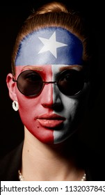 Portrait of woman with painted Texas USA state flag with sunglasses on black