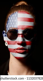 Portrait of woman with painted USA Flag with sunglasses on black