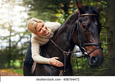 Portrait of a woman patting her horse while in saddle