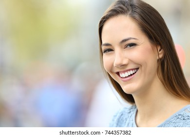 Portrait of a woman with perfect smile and white teeth looking at you on the street with copy space