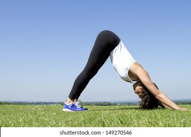 Portrait of a Woman Performing Downward Dog Yoga Pose Outdoors