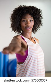 Portrait of woman performing stretching exercise in gym