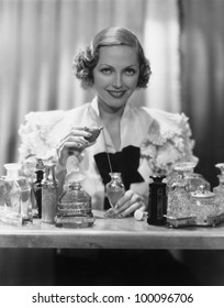 Portrait of woman with perfume bottles