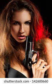 Portrait of woman with pistol in studio on black background