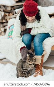 Portrait of a woman playing with her kitten outside a cottage on a cold winter day. Cropped image of a woman stroking a cat in the snow.