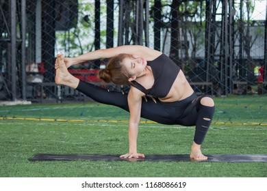 Portrait of woman is playing yoga in black sportwear.