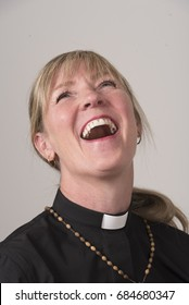 Portrait of a woman priest with blond hair and a big smile