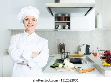 Portrait of the woman proffesional who is posing in the kitchen at the cafe.