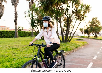 Portrait of a woman with protective safety mask on her face riding a bike on a bike path in the city on a sunny day.