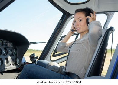 portrait of woman putting on headset in helicopter
