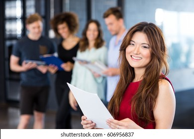 Portrait of woman reading a document while colleagues standing behind in office