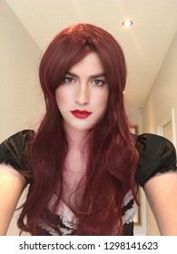 Portrait of a woman with red hair. Beautiful sensual crossdresser. A man in a woman's dress. Sissy. Red lips