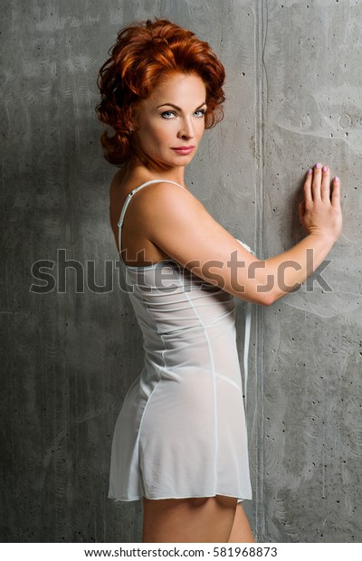 Portrait of a woman with red hair. The picture was taken in a studio on a background of a concrete wall.