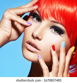 Portrait  of a woman with  red hairs and multicolor nails. Closeup face of pretty girl with glamour makeup of eyes. Studio photo.