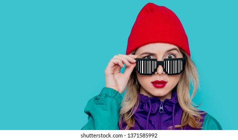 Portrait of a woman in red hat, sunglasses with barcode and suit of 90s on blue background.