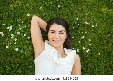 Portrait of woman relaxing with hand behind head on grassland in park