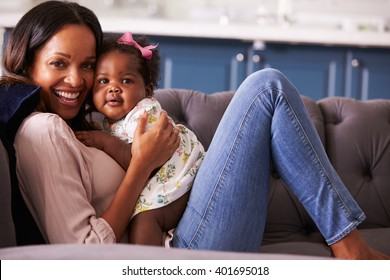 Portrait of woman relaxing at home with her toddler daughter