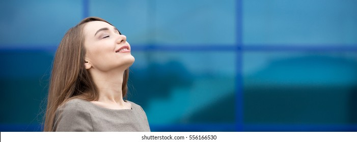 Portrait woman relaxing outdoors with closed eyes. Happy beautiful woman breathing fresh air on the street in summer. Horizontal photo banner for website header design with copy space for text