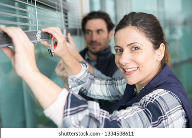 portrait of woman repairing a window blind