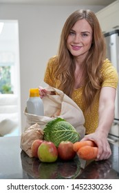 Portrait Of Woman Returning Home From Shopping Trip Unpacking Plastic Free Grocery Bags