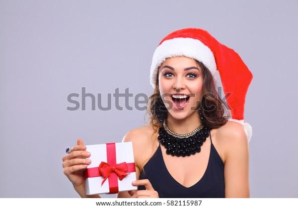 Portrait of woman in Santa hat holding gift box, isolated on white background