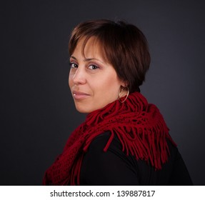 Portrait of a woman with short-cut red hair wearing red scarf looking back. Close-up studio portrait on the gray background.