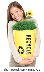 Portrait of woman showing recycle bin with grass and flower. Recycling concept. Young smiling asian / caucasian woman isolated on white background.