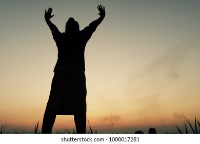 Portrait of woman silhouette is standing and celebrating life at sunset background