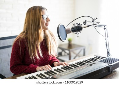 Portrait of woman singer playing electric piano and singing a song into mic on online radio